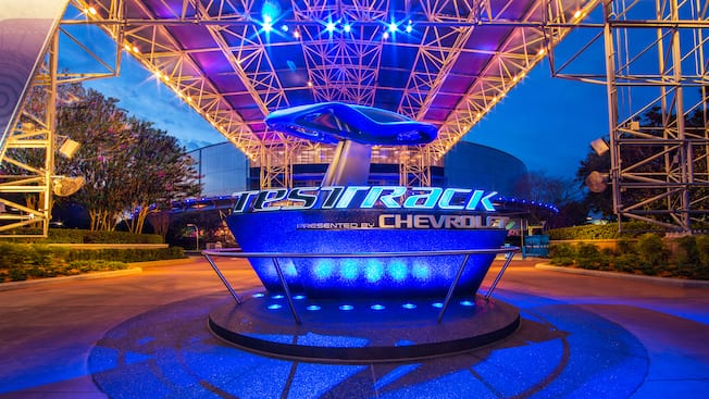 Outdoor sign and entrance to Test Track Presented by Chevrolet lit up at night at Epcot