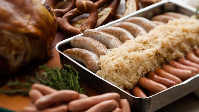 Pan relleno con chucrut y 2 tipos de salchichas alemanas sobre una tabla junto a carnes y pretzels