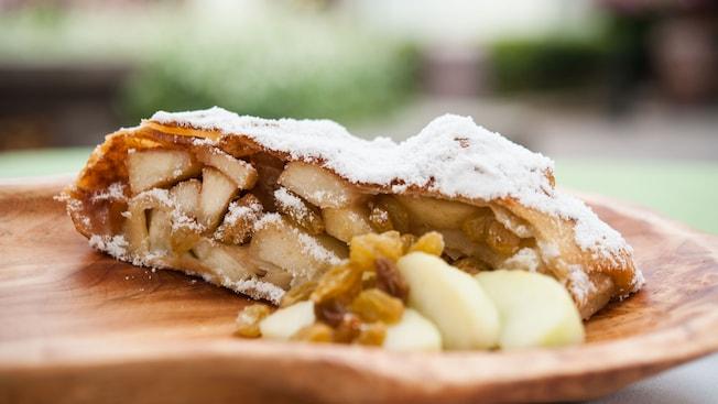 Coupe d'un strudel aux pommes et aux raisins jaunes, saupoudré de sucre glace