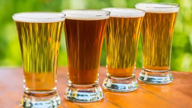 Quatro copos de cerveja sobre uma mesa de madeira