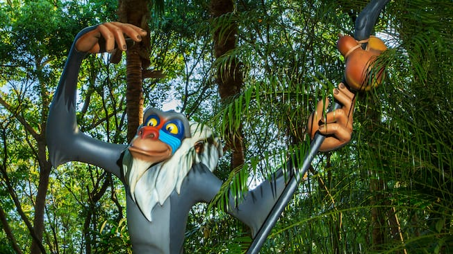Rafiki the baboon holds his staff in front of jungle trees