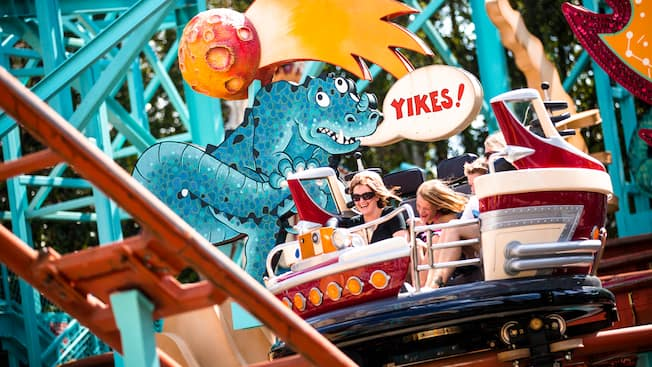 A mother and daughter spin while sliding on the tracks at the Primeval Whirl attraction