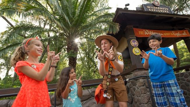 Una líder de la tropa de Wilderness Explorer enseña a los niños una seña especial de manos