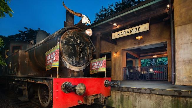 """Um trem com bandeiras indicando """"Wildlife Express"""" na plataforma da estação com uma placa que diz """"Harambe"""""""