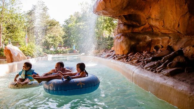 Pai e seus 2 filhos em boias separadas relaxam perto de uma cachoeira no Cross Country Creek