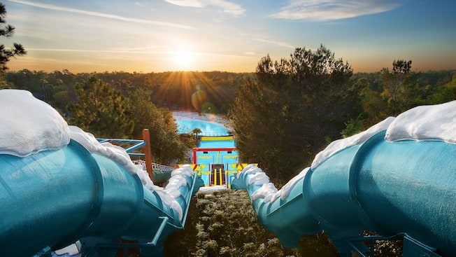 Downhill Double Dipper, side-by-side enclosed waterslides, with the sun rising on the horizon