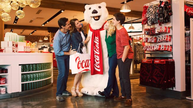Four friends gather around the Coca Coca Polar Bear on the second floor of the Coca Cola Store at Disney Springs