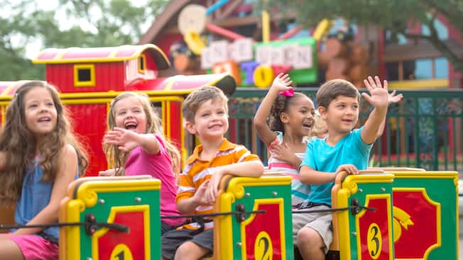 A half dozen young boys and girls smile and wave as they ride the Marketplace Train at Disney Springs