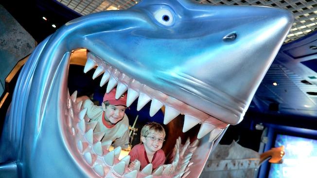 "Dos jóvenes sonríen desde adentro de las mandíbulas de Bruce the Shark en Disney's ""Little Nemo"" en SeaBase de Epcot"