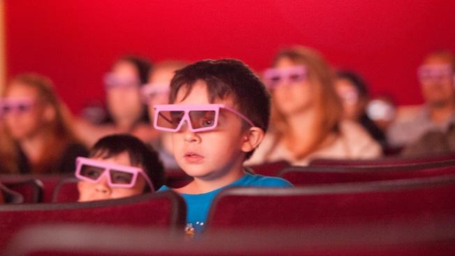 Deux jeunes enfants portent des lunettes 3D et regardent un film