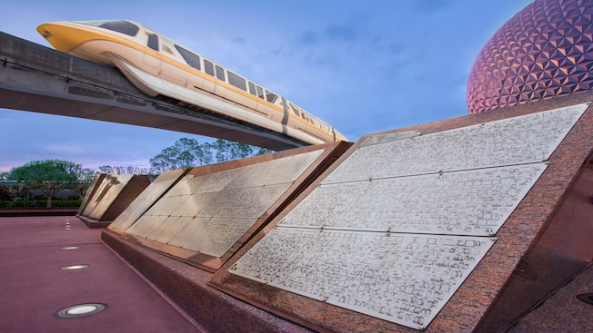 A row of Leave a Legacy stone monoliths with a monorail train and Spaceship Earth in the background