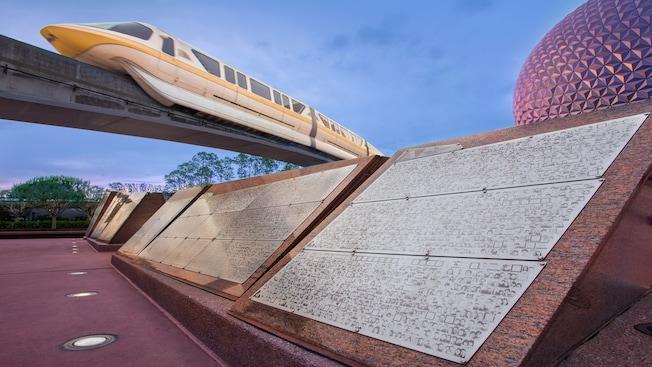 Una fila de monolitos de piedra de Leave a Legacy con un tren monorriel y Spaceship Earth de fondo