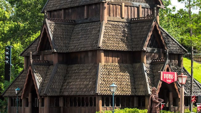 A Viking statue stands in front of a replica of Gol Stave Church