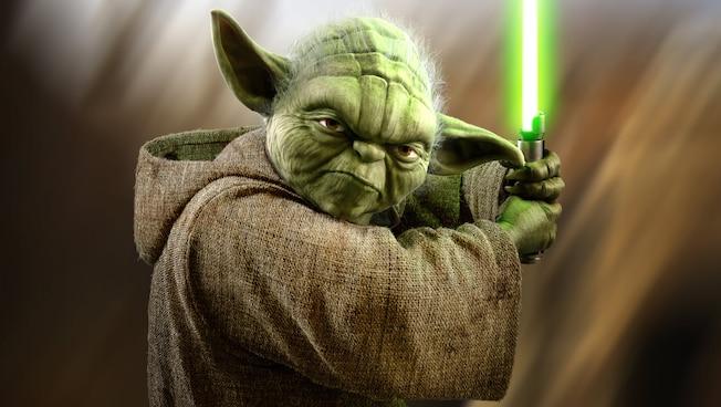 Yoda faz uma careta segurando seu sabre de luz como um taco de beisebol