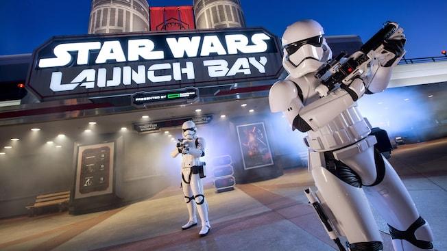 Dos Stormtroopers imperiales con rifles hacen guardia frente a una marquesina iluminada de Star Wars Launch Bay