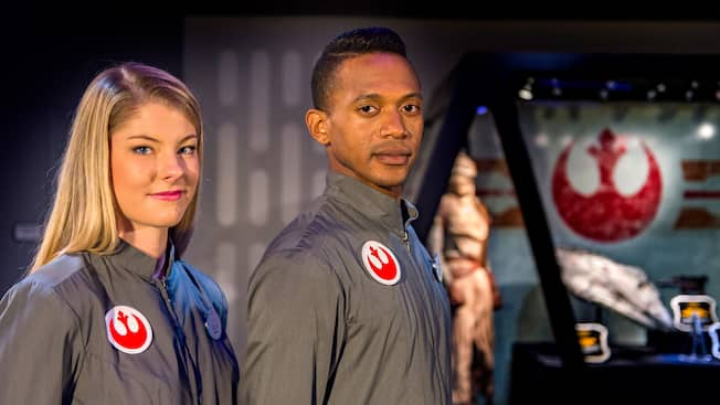 A woman and a man with Rebel Alliance symbol patches on their shirts