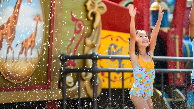 A little girl in a bathing suit delights while being splashed at Casey Jr. Splash 'N' Soak Station