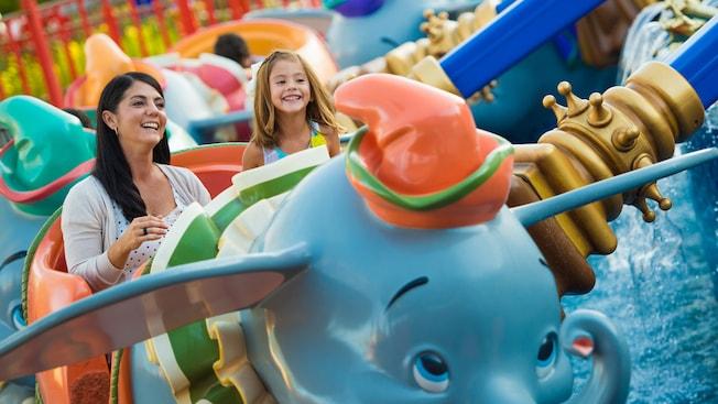 Una madre y su hija dan un alegre paseo en un vehículo con la apariencia de Dumbo en Dumbo the Flying Elephant