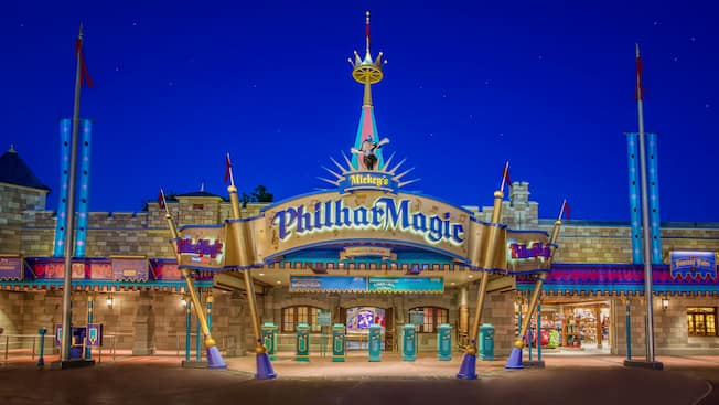The sign and entrance to Mickey's PhilharMagic at the Fantasyland Concert Hall at night