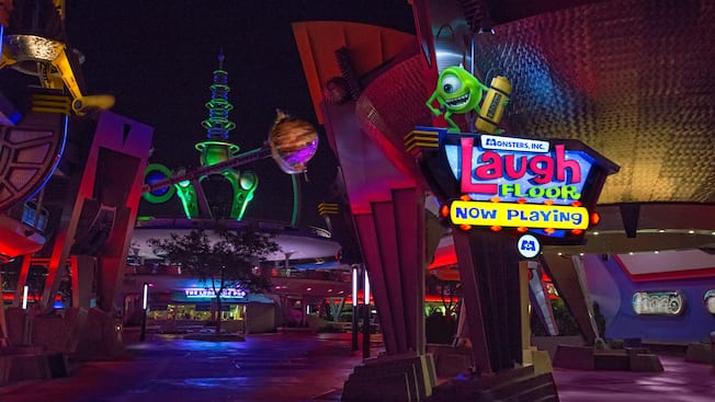 A statue of Mike Wazowski stands atop a sign for Monsters, Inc. Laugh Floor in Tomorrowland at night