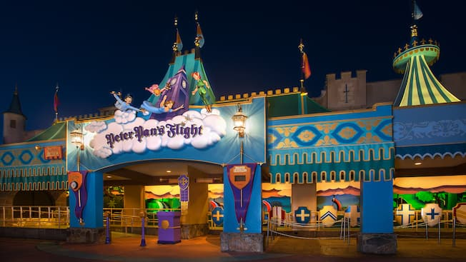 Night view of Peter Pan's Flight with statues of Peter Pan, Wendy and her brothers above its sign