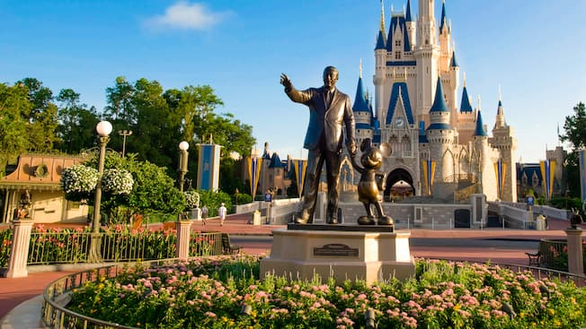 Partners statue of Walt Disney holding hands with Mickey Mouse in front of Cinderella Castle