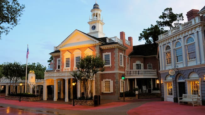The Colonial brick building of the Hall of Presidents has a clock tower with a bell and a weather vane