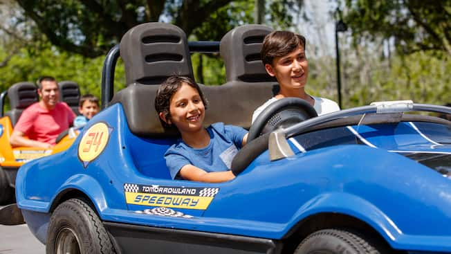 Two brothers drive in a car at Tomorrowland Speedway in Magic Kingdom park