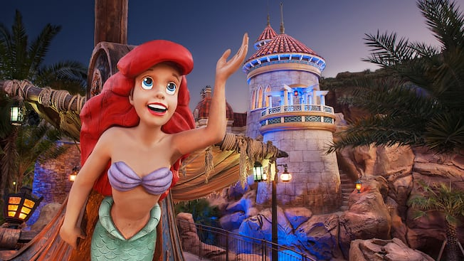 A figurehead of Ariel in front of Under the Sea ~ Journey of The Little Mermaid at night