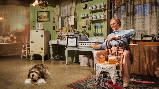Un hombre y un perro de Audio-Animatronic sentados en una casa con los electrodomésticos más recientes de la década de 1920