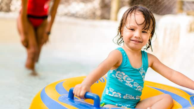 A little girl in a bathing suit holds on tightly to an inner tube