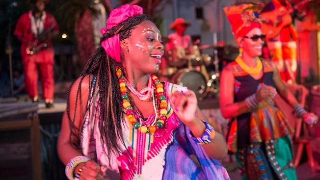 Dos mujeres artistas con vestidos y adornos festivos al estilo africano bailan felices en el escenario mientras, al fondo, los músicos tocan los instrumentos
