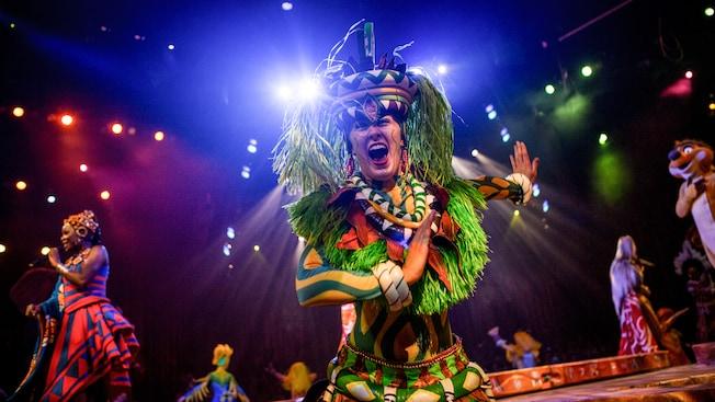 Artistas fantasiados do Festival of the Lion King acenam do palco