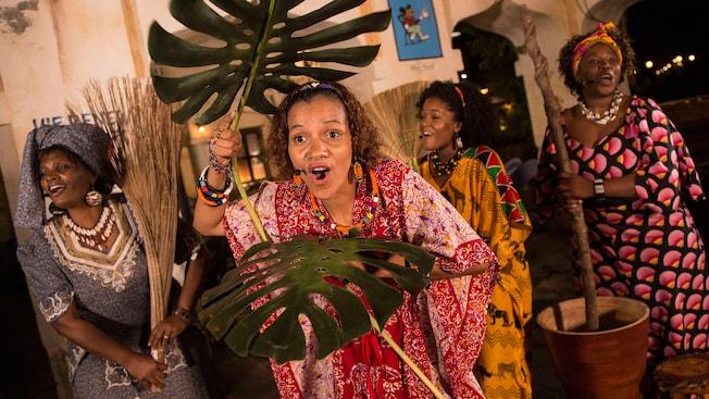 Un grupo de mujeres artistas vestidas con ropas tradicionales africanas cantan mientras utilizan plantas y escobas artesanales como piezas de utilería