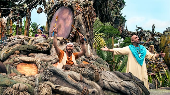 3 performers stand by a large tree in Pandora The World of Avatar