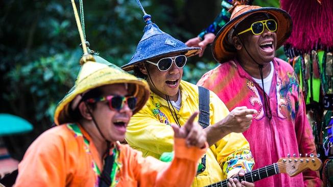 Tres miembros de la banda callejera Viva Gaia vestidos con colores vibrantes participa en una impactante actuación musical