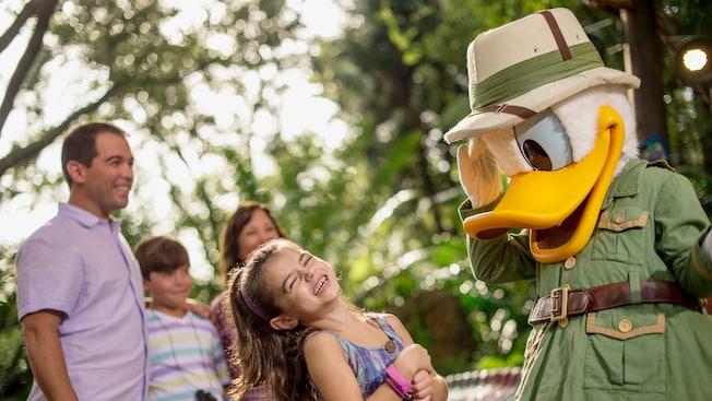 Pato Donald vestido com roupas e chapéu de safári cumprimenta uma garotinha encantada enquanto sua família sorri