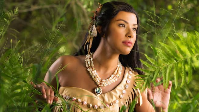 Disney Princess Pocahontas wears a one shoulder dress, feathers in her hair and beaded necklace while looking out from the forest
