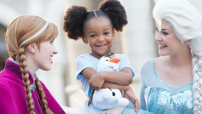 A little girl with an Olaf plush toy stands between Princess Anna and Queen Elsa