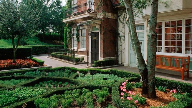 Un paisaje inglés con un jardín muy cuidado junto a un edificio de ladrillos, con barandillas decorativas