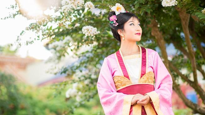 Mulan viste una bata china colorida y flores en su cabello mientras mira a la distancia