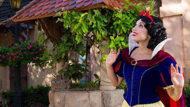 Snow White stands in a garden and looks up at the sky at Meet Snow White in Germany at Epcot