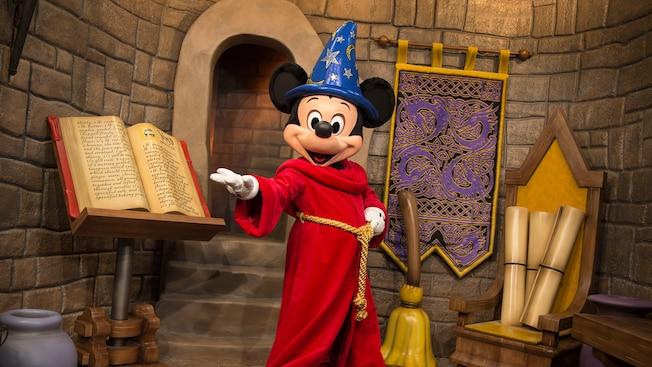 Mickey Feiticeiro parado com uma mão estendida em uma área de encenação, preparada para ter a aparência de um castelo com um livro de feiticeiro, pergaminhos e vassoura de aprendiz