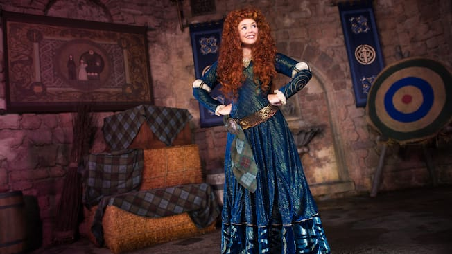 Merida stands in a castle-like room at Meet Merida Fairytale Garden in Fantasyland