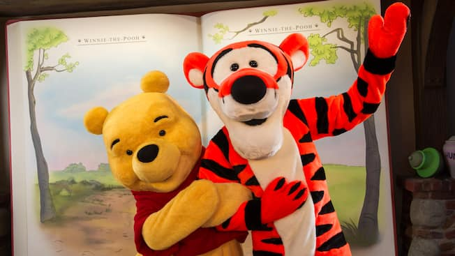 Winnie the Pooh and Tigger arm-in-arm near the Many Adventures of Winnie the Pooh in Fantasyland