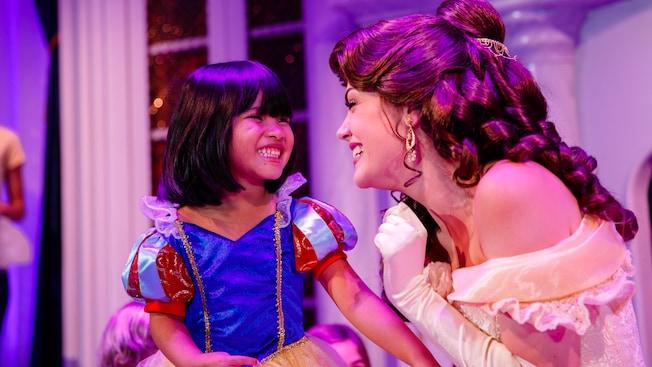 Uma garotinha vestida de Branca de Neve sorri quando se encontra com a Bela