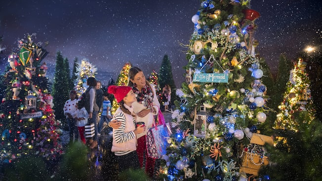 multiple families look at decorated christmas trees that have signs on them that read little mermaid disney springs marketplace - When Is Disney Decorated For Christmas