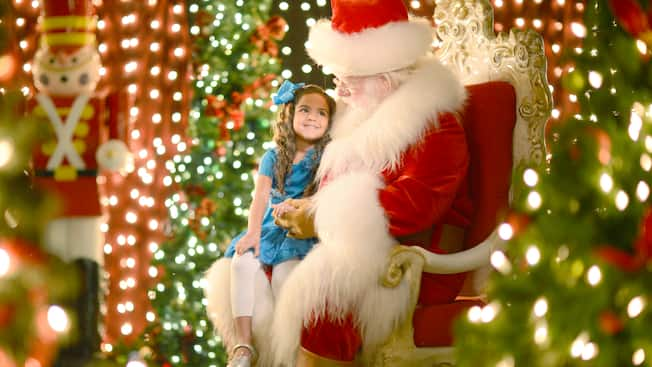 A little girl sits on Santa's knee and smiles at him surrounded by glittering Christmas lights