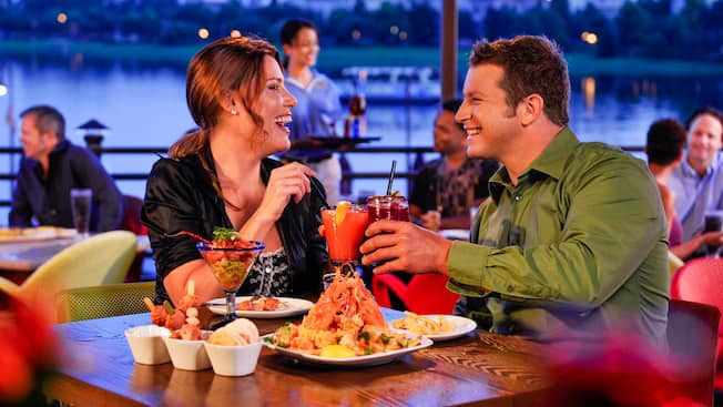 A woman and man share a laugh as they toast over their dinner
