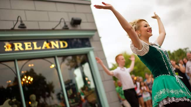 Two Irish dancers raise their arms to the sky after finishing a performance
